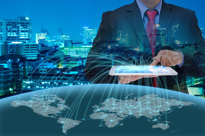 Digital composite image of businessman holding tablet showing world map against illuminated cityscape at dusk