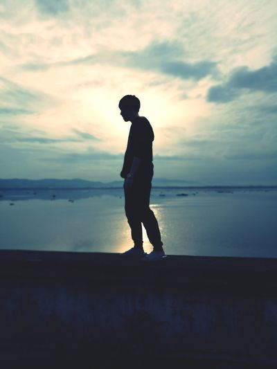 Silhouette man standing on retaining wall against sea