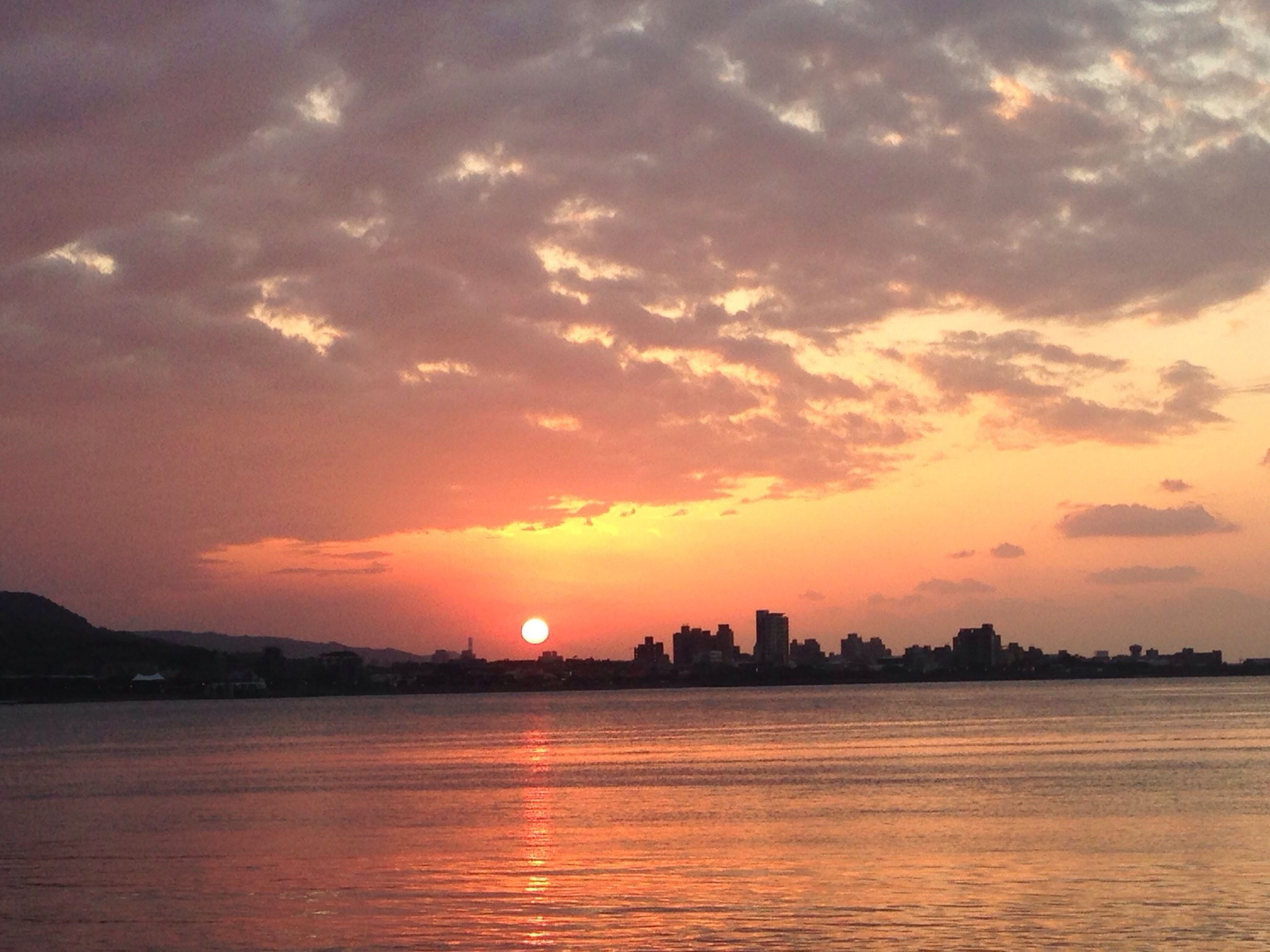sunset, waterfront, water, orange color, sky, scenics, silhouette, sea, beauty in nature, building exterior, tranquil scene, sun, tranquility, architecture, cloud - sky, built structure, idyllic, reflection, nature, city