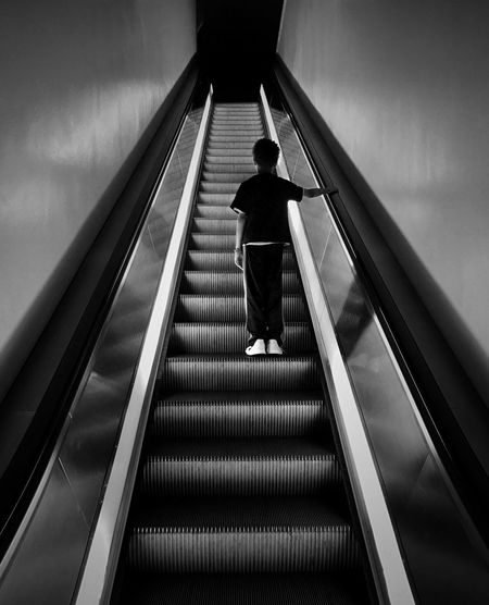 Rear View Of Boy Standing On Escalator