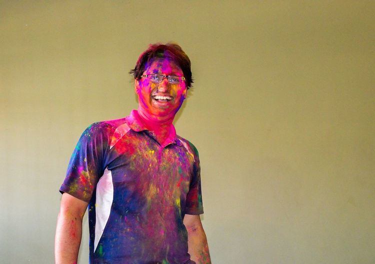 Portrait of cheerful mid adult man covered in multi colored powder paint against wall