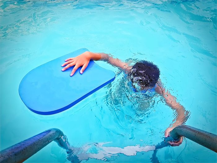 High Angle View of A Boy Practicing Swimming and Diving Diving Practice Blue Board Boys Child Childhood Day Enjoyment Human Arm Leisure Activity Lifestyles Males  Men Nature One Person Outdoors Pool Real People Swimming Swimming Pool Turquoise Colored Water Waterfront