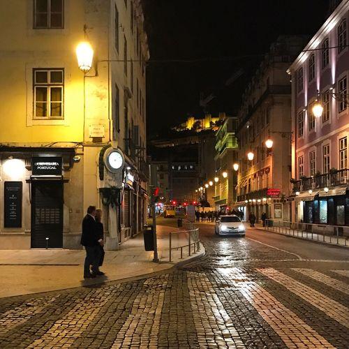 Man walking on illuminated street at night