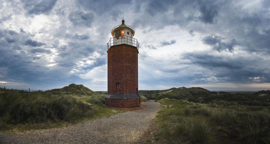 Lighthouse amidst field against sky