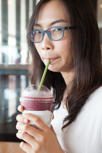 Close-up portrait of young woman drinking smoothie