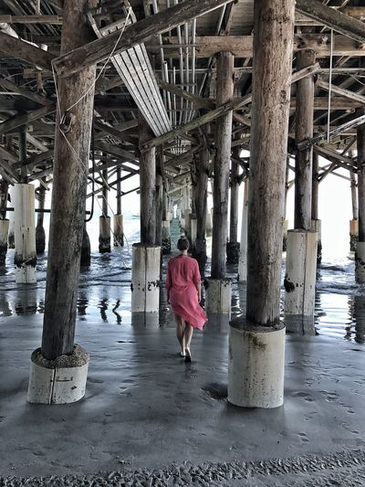 Rear view of a woman walking under pier at beach