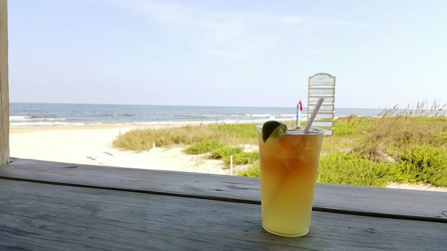 Drink on wooden plank by beach against sky