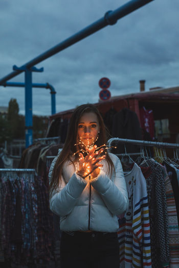 Portrait of young woman holding illuminated lighting equipment at clothes market