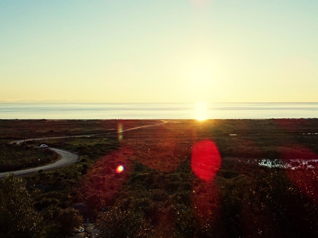 sunset, lens flare, sun, scenics, sea, nature, water, beauty in nature, horizon over water, tranquility, sky, sunlight, tranquil scene, clear sky, no people, outdoors, beach, landscape, day