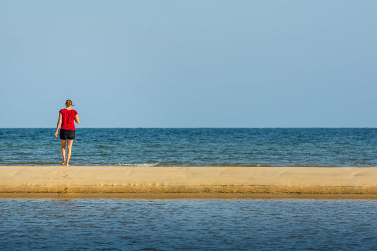 A young women walks along a sand back towards a calm sea. Alone Beach Clear Sky Copy Space Day Full Length Holiday Horizon Horizon Over Water Land Leisure Activity Looking At View Nature One Person Rear View Red Clothes Scenics - Nature Sea Sky Trip Vacations Water Women