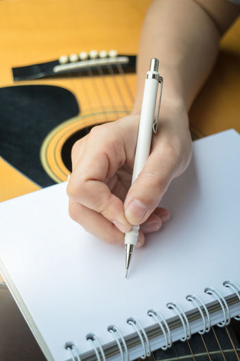 Cropped Hand Of Woman With Guitar Writing On Book