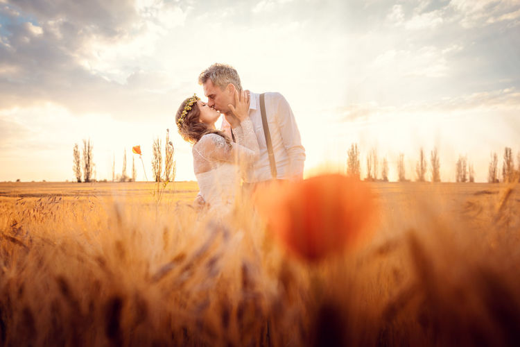 Wedding couple kissing in romantic setting on a wheat field during sunset