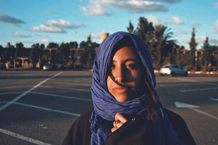 Portrait of young woman standing on road against sky