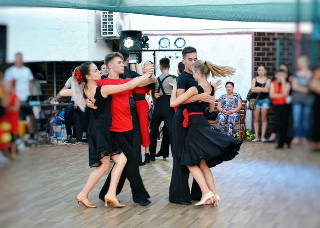 Young Men Women Lifestyles Togetherness Dance Dancing Leisure Activity Young Women Teamwork Young Adult Sports Team Outdoors Music Arts Culture And Entertainment Skill  Ballroom Dancing Dance Floor Dancer Motion Real People Large Group Of People Performance Enjoyment People