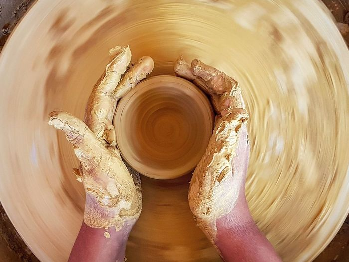 Cropped Hands Of Potter Shaping Earthenware On Pottery Wheel