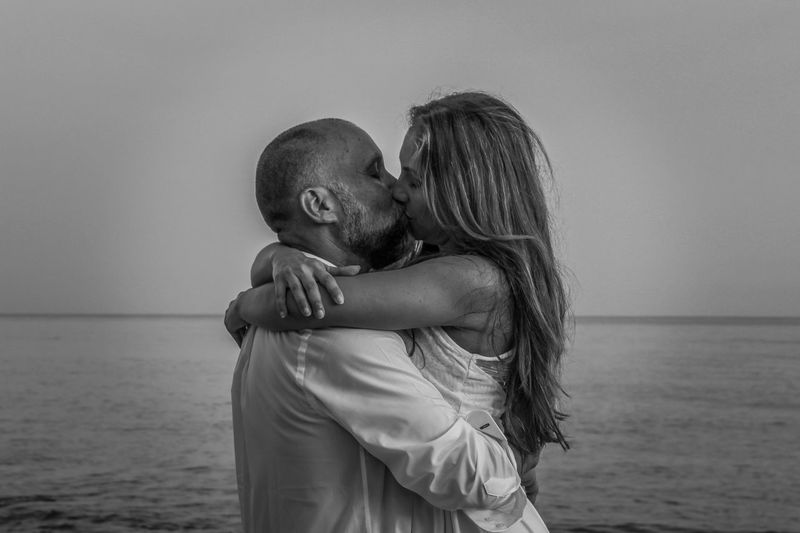 Side View Of Couple Kissing While Standing At Beach Against Sky