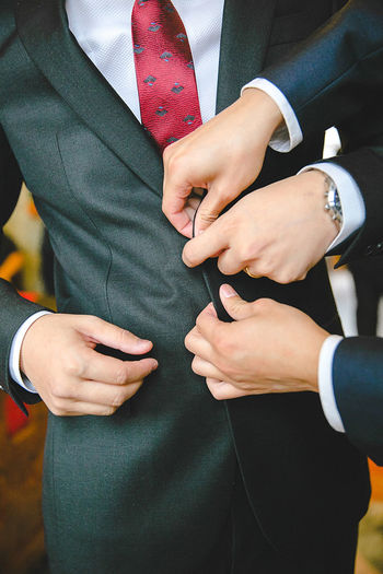 Cropped image of best man buttoning groom during wedding