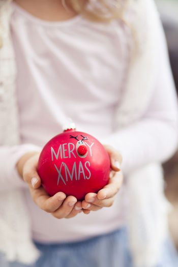 Midsection of woman holding bauble