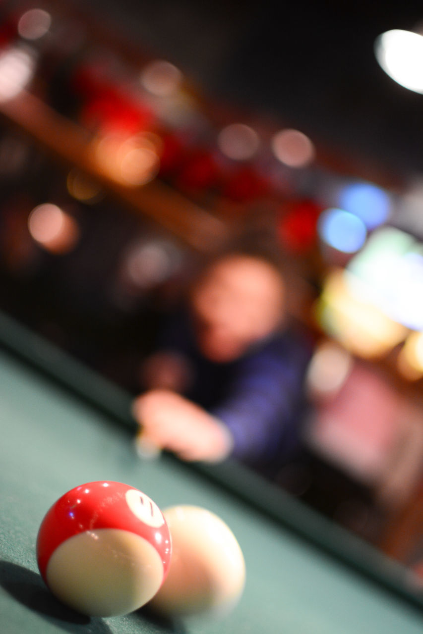 table, indoors, focus on foreground, ball, pool ball, pool table, close-up, incidental people, leisure activity, sport, red, illuminated, pool - cue sport, selective focus, real people, food and drink, one person, sphere, still life
