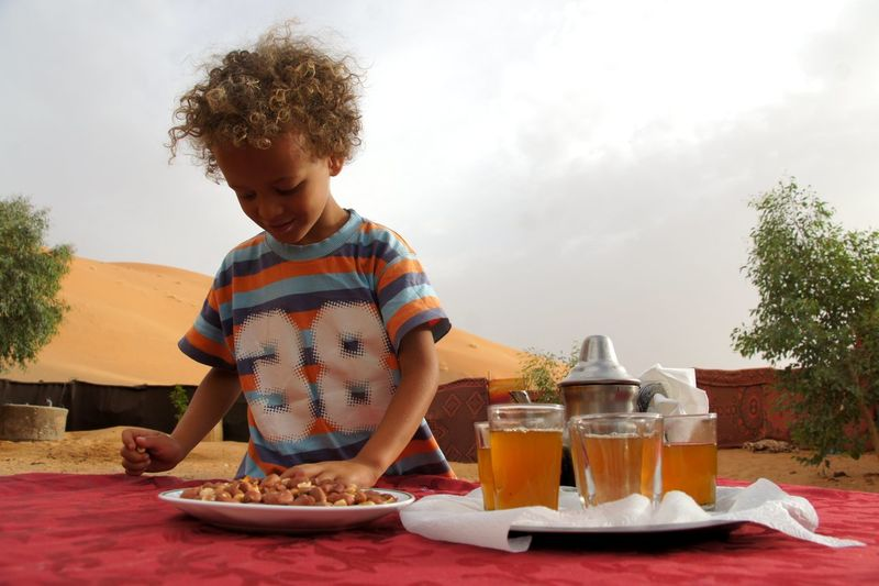 Boy standing by mint tea glass at desert against sky