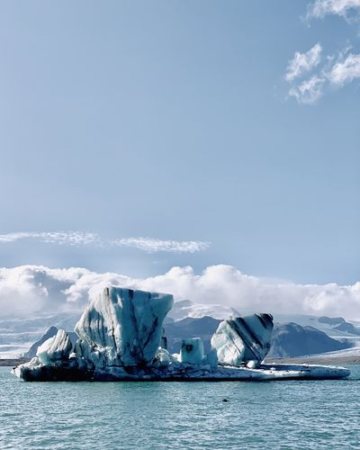 Scenic view of iceberg against sky during winter