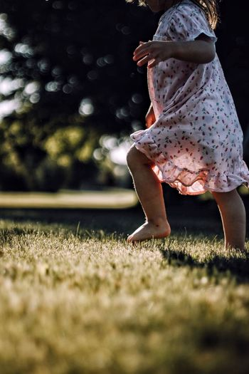 Low Section Of Girl Walking On Grassy Field