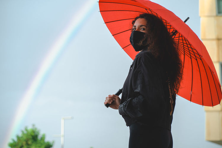 Woman with umbrella standing against the background