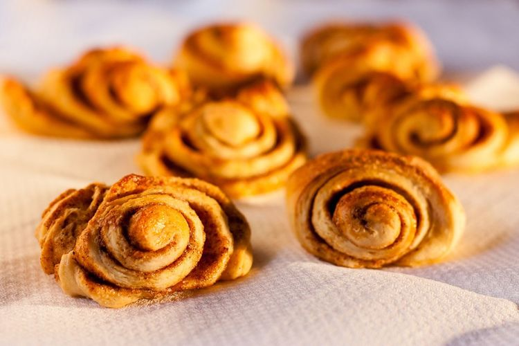 Close-up of fresh baked cinnamon buns on tissue paper
