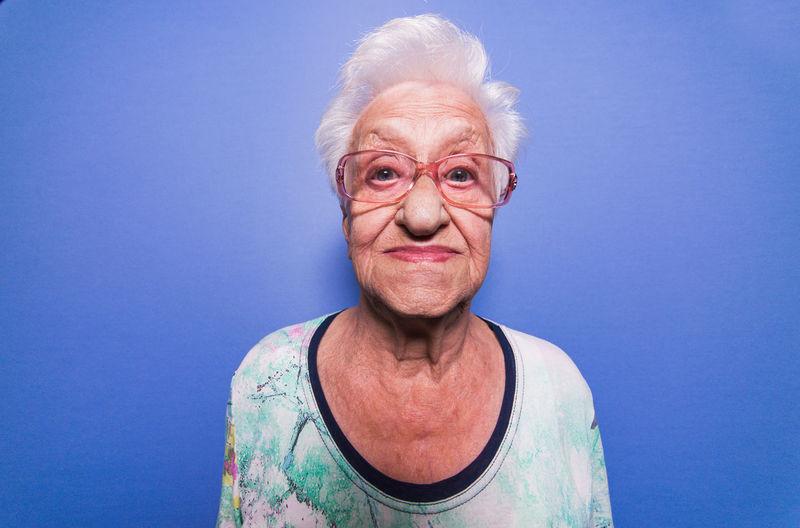 Portrait of senior woman wearing eyeglasses against blue background