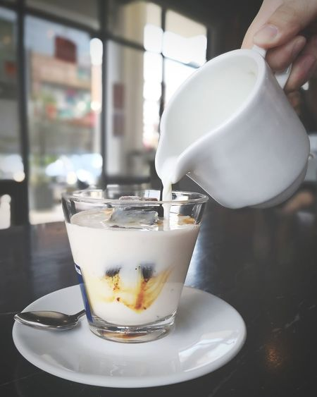 Close-up of hand pouring milk in coffee cup on table