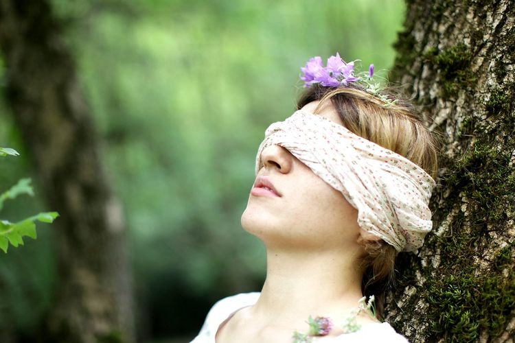 Close-up of woman with blind fold leaning on tree trunk