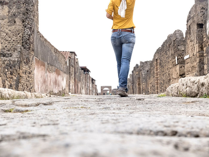 Low section of man walking on wall
