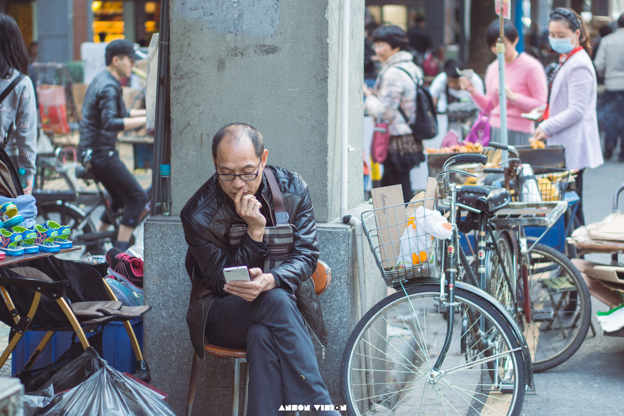 real people, incidental people, bicycle, communication, day, lifestyles, city, senior men, focus on foreground, outdoors, city life, senior adult, wireless technology, mobile phone, men, technology, one person, people, adult