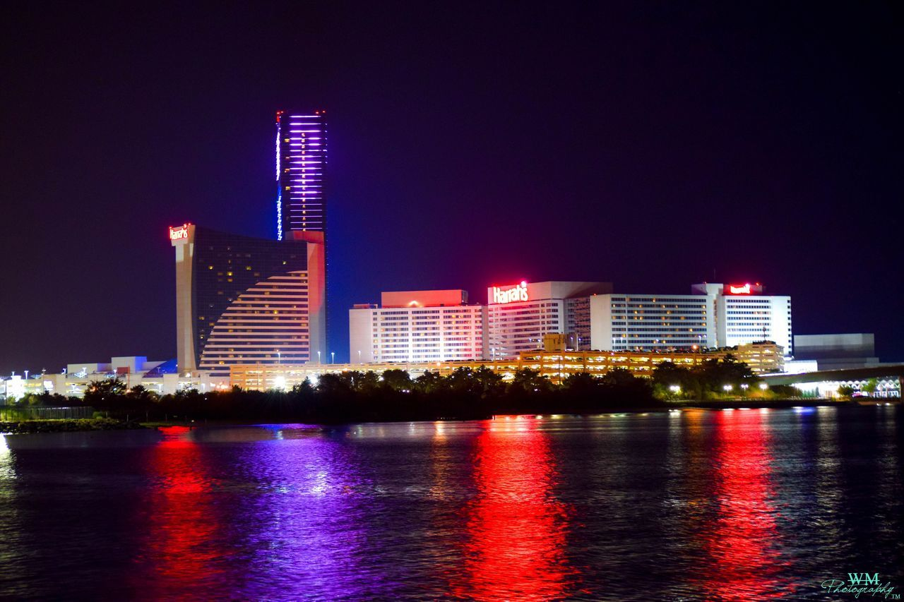 building exterior, illuminated, architecture, night, built structure, skyscraper, city, modern, waterfront, water, reflection, urban skyline, travel destinations, no people, outdoors, cityscape, sky, multi colored