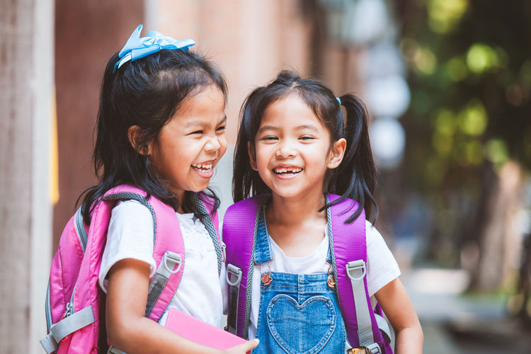 Two cute asian child girls with backpack eating pancake together after school in the school Accessory Adorable Asian  Backpack Bag Book Brotherhood Cheerful Child Curious Cute Daughter Development Education Elementary Enjoy Environment Equipment Family Friend Fun Generation Girl Happy Hold Kid Knowledge Laugh Learn Lifestyle Love Nature Outdoor People Play Portrait Primary Pupil School SchoolGirl Sibling Sister Smile Student Study Talk Thai Together Twin Young