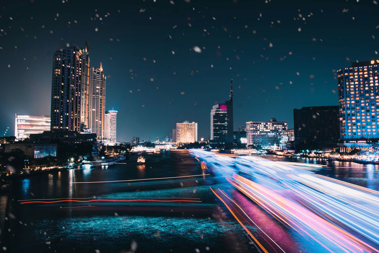 Light trails on illuminated buildings in city against sky at night