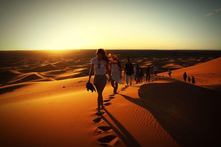 Full Length Of People Walking On Sand In Desert During Sunset