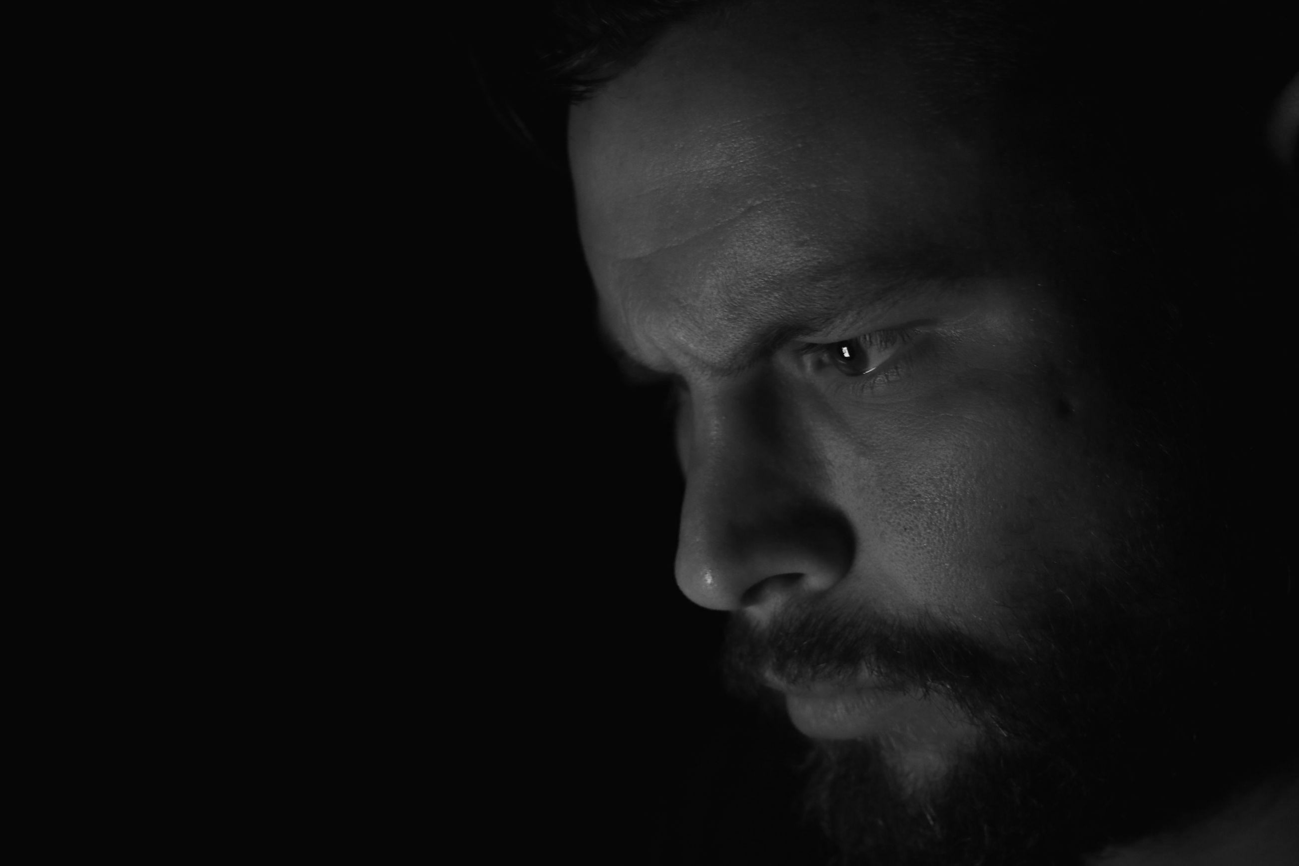 one person, headshot, indoors, black background, portrait, close-up, looking away, studio shot, men, young men, looking, human face, serious, human body part, body part, males, facial hair, lifestyles, mid adult men, contemplation