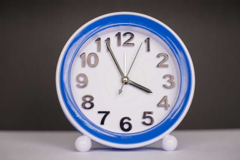 Plastic cheap alarm clock in a dual tone background. Alarm clock sales are down since the introduction of cell phones Alarm Clock Alarm Clocks Black And White Black Background Blue Cheap Circle Clock Close-up Colors Four O'clock Geometric Shape No People Plastic Still Life Time Time Concepts