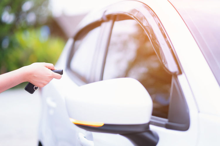 Closeup woman hand holding the remote control car alarm systems Human Hand Hand One Person Holding Mode Of Transportation Real People Land Vehicle Lifestyles Human Body Part Car Motor Vehicle Transportation Adult Day Communication Unrecognizable Person Women Body Part Technology Finger