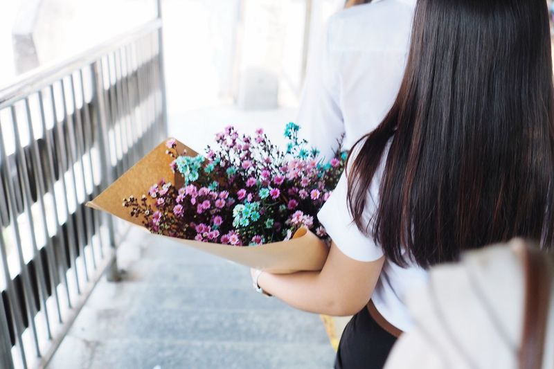 The back of the girl holding a bouquet of dried tiny flowers by her left arm. Bouquet EyeEm Selects Flower Real People Flowering Plant One Person Day Plant Lifestyles Women Standing Holding