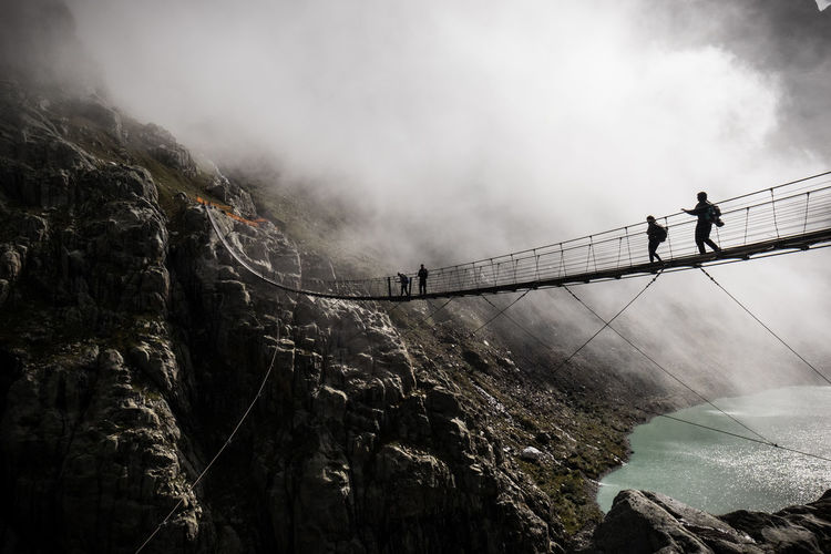 Low Angle View Of People On Footbridge Against Mountains