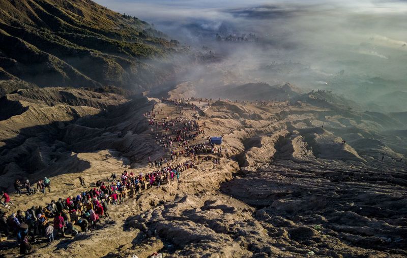 High angle view of crowd on rock by land