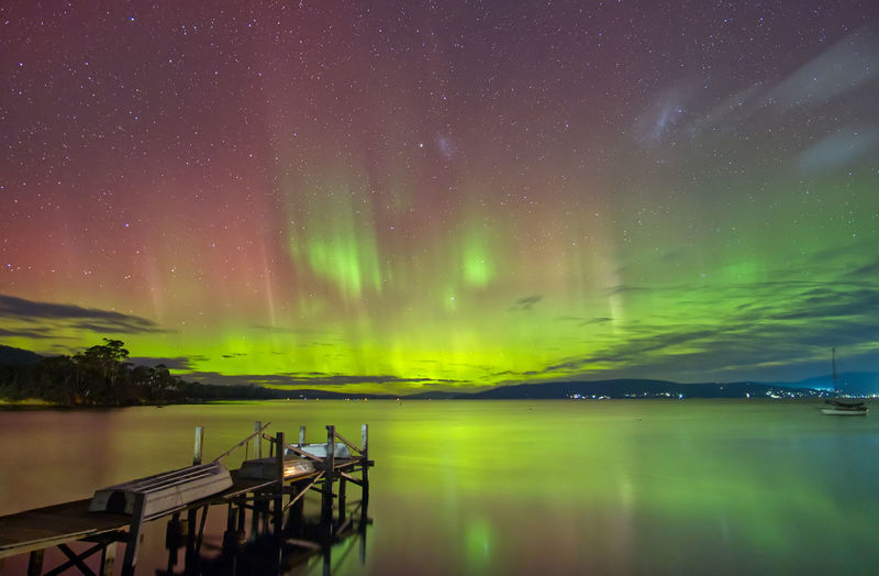 Scenic view of aurora australis southern lights over lake against sky at night