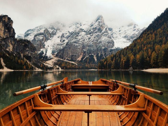 Boat in pragser wildsee against snowcapped mountain
