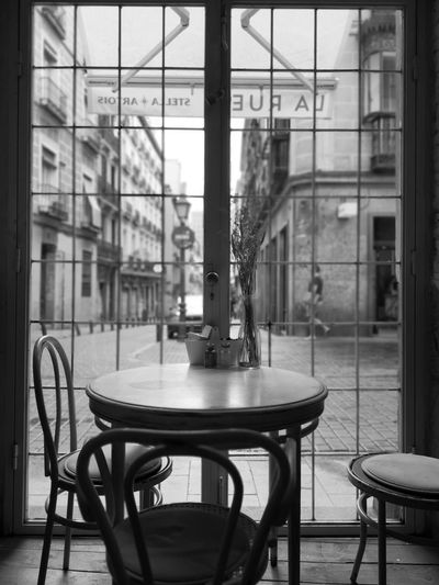 City City Street EyeEm Gallery Eyemphotography Streetphotography Lifestyles Blackandwhite Black And White Cafe Flowers Chair Table Window Architecture Built Structure Transparent Glass - Material