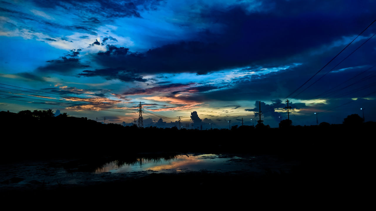 SILHOUETTE ELECTRICITY PYLONS AGAINST DRAMATIC SKY