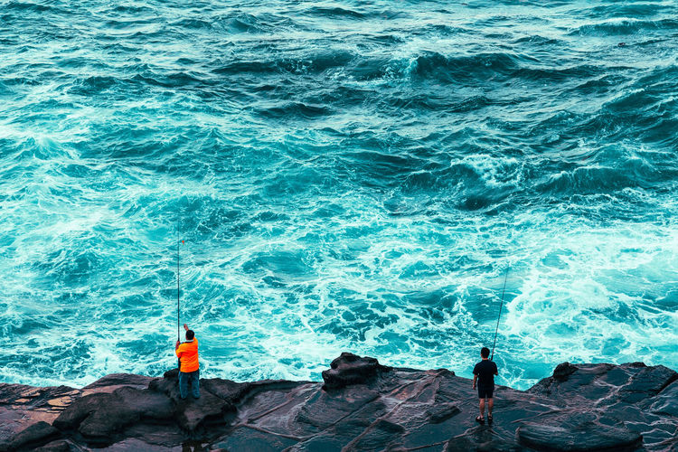 Rear view of men fishing at sea shore
