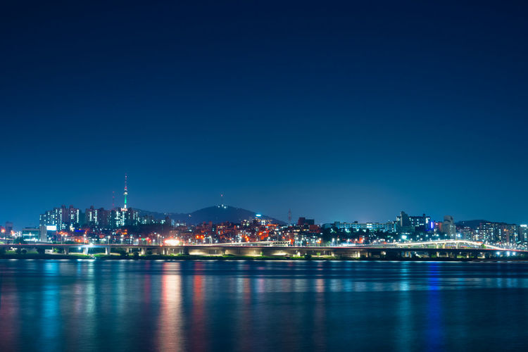 Illuminated buildings by hanriver against blue sky at night in korea