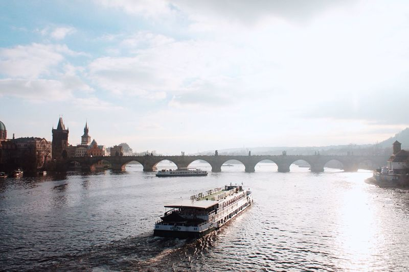 Boat moving towards charles bridge in vltava river against cloudy sky